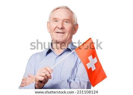 Senior man with Swiss flag. Cheerful senior man holding flag of Switzerland and smiling at camera while standing against white background - stock photo
