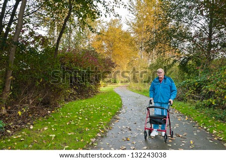 Senior Man with Walker on Hiking Trail in Park - stock photo