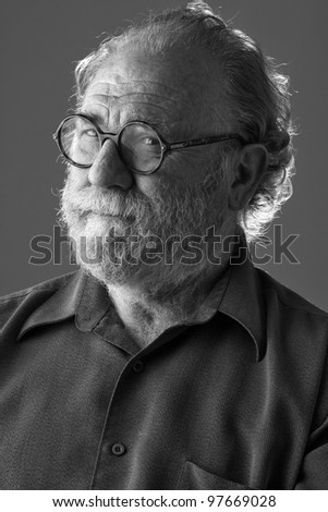 Senior man with watchful expression narrows his eyes and tenses mouth. Low key monochrome, vertical layout with copy space. - stock photo