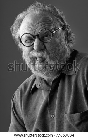 Senior man with white beard and round glasses sticks out tongue. Monochrome, vertical layout with copy space. - stock photo