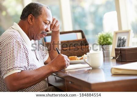 Senior Man Writing Memoirs In Book Sitting At Desk - stock photo