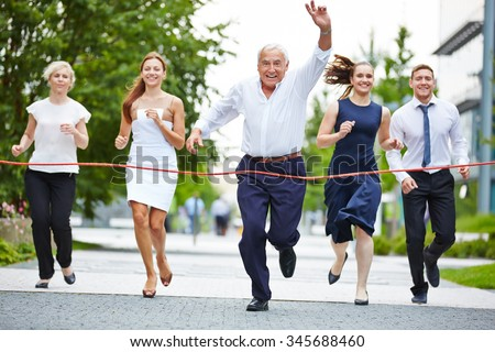 Senior manager cheering when taking leadership in a business race to the finish line - stock photo