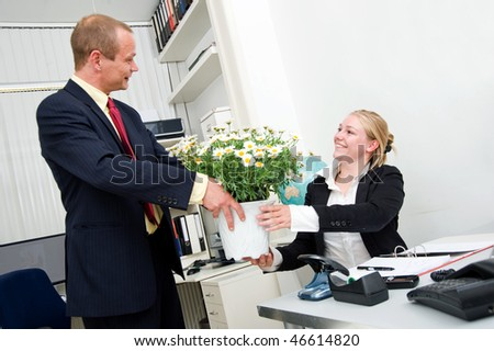 Senior manager giving his younger female associate a large flower pot with white daisies