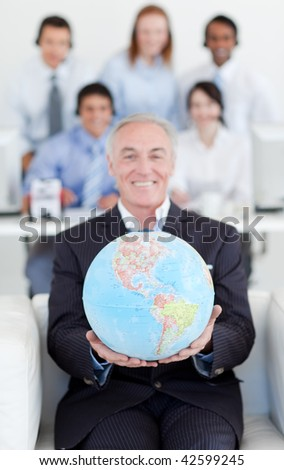 Senior manager holding a terrestrial globe with his team in the background - stock photo
