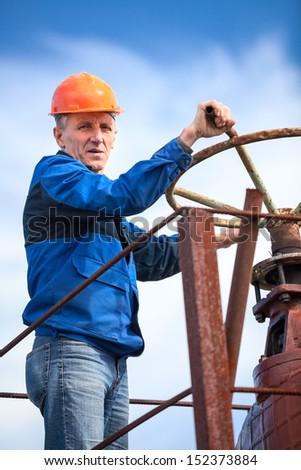 Senior manual worker turning huge valve gate at factory - stock photo