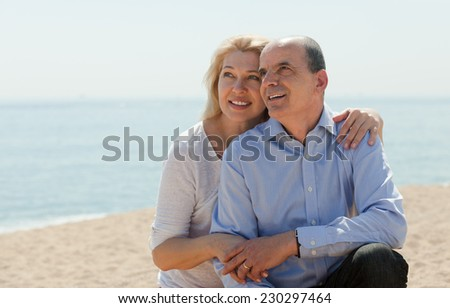 Senior mature couple in love at sea shore in warm season - stock photo