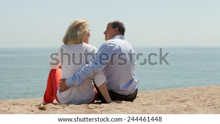 Senior mature couple sitting on sand at beach and enjoying the view - stock photo