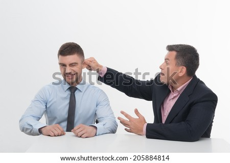Senior mature manager chief sitting at desk pulling his young junior employee ear, isolated on white