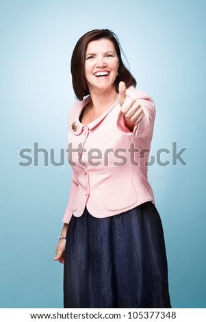 senior mature woman giving thumbs up sign success