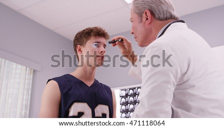 Senior medical doctor checking basketball player's eyes with flashlight.