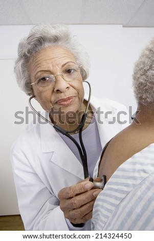 Senior medical practitioner examines breathing with stethoscope - stock photo