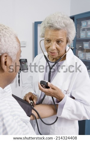 Senior medical practitioner takes blood pressure - stock photo