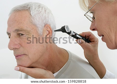 senior medical visit - hear examination with special lamps - stock photo