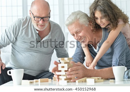 senior men and granddaughter with  board game - stock photo