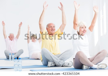Senior men and women during fitness classes, stretching their arms while sitting with crossed legs on exercise mats - stock photo