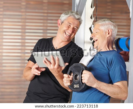 Senior men exercising in gym and laughing with tablet PC - stock photo