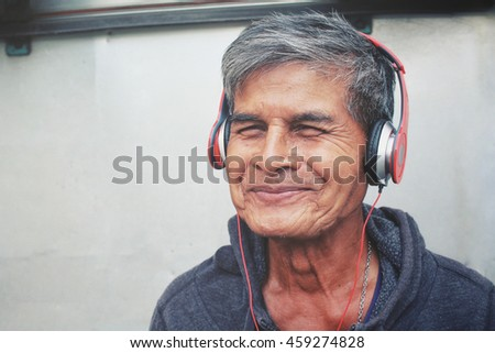 Senior men listen to music on headphones