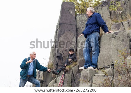 Senior men with child boy trekking on rocky terrain.