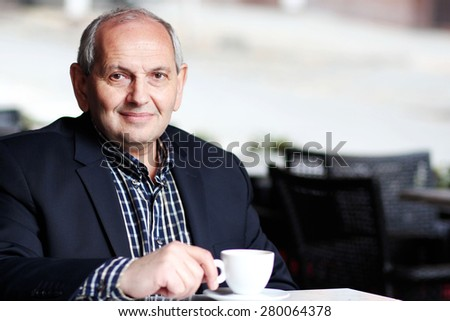 Senior middle-aged man sitting on a summer terrace of a cafe, drinking coffee  - stock photo