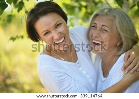 senior Mother and her nice daughter in  park - stock photo