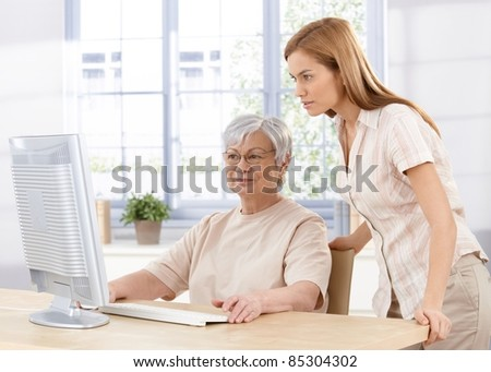 Senior mother and young daughter using computer at home, looking at screen.?
