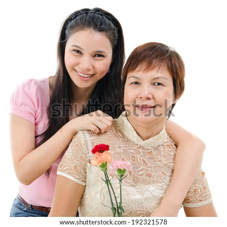 Senior mother holding carnation flower, adult daughter embraces mom, isolated on white background. Mixed race Asian family portrait.  - stock photo