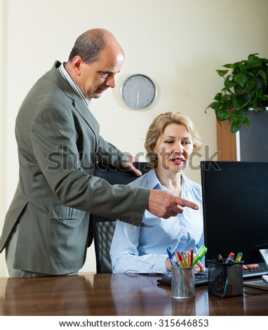 Senior office manager scolding aged female secretary for mistake