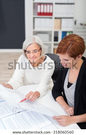 Senior Office Woman with Document Trains her New Female Colleague at the Workplace. - stock photo