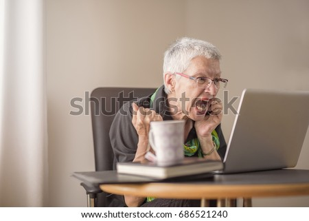Senior old woman screaming at her laptop, enraged with news
