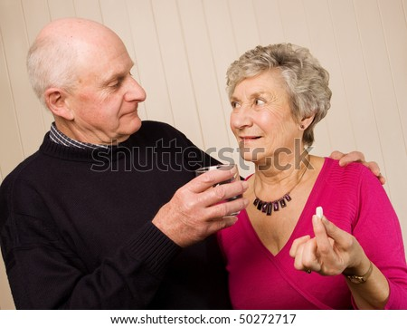 Senior older mature couple taking pain medication with glass of water - stock photo