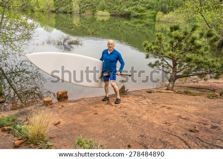 senior paddler carrying paddleboard and paddle on a rocky shore of a lake - Horsetooth Reservoir, Fort Collins, Colorado - stock photo