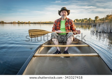 senior paddler enjoying paddling a canoe on a calm lake, Riverbend Ponds Natural Area, Fort Collins, Colorado