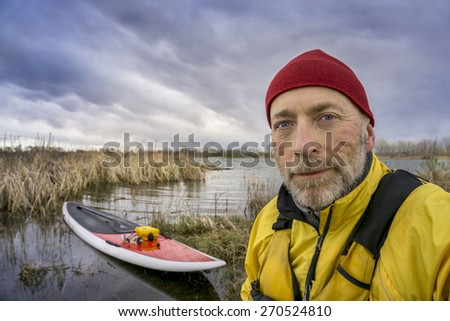 senior paddler in life jacket with his paddleboard and lake in background, early spring scenery with stormy sky in Colorado - stock photo