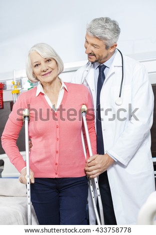 Senior Patient Being Helped By Doctor With Crutches
