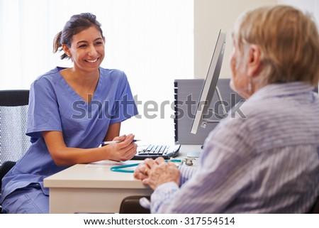Senior Patient Having Consultation With Nurse In Office - stock photo