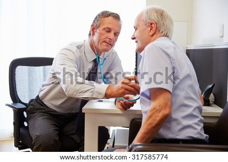 Senior Patient Having Medical Exam With Doctor In Office - stock photo