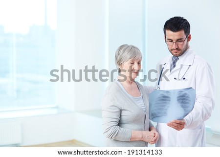 Senior patient looking attentively at x-ray held by radiologist in hospital