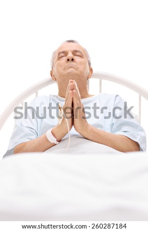 Senior patient praying in a hospital bed with an iv drip attached to his hand - stock photo