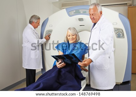 Senior patient with x-ray image and doctors at MRI scan in radiology