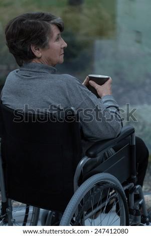 Senior pensive woman on wheelchair drinking hot tea - stock photo