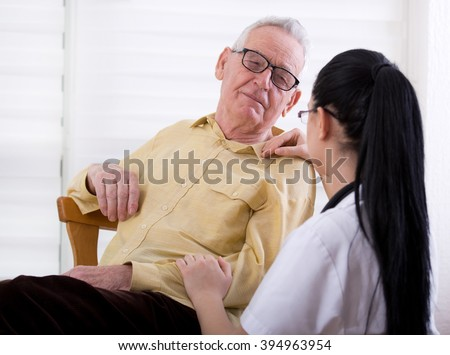 Senior people care concept. Young nurse holding senior smiling man for hand and shoulder - stock photo