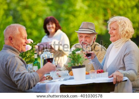 Senior people celebrating birthday in garden with cake and wine - stock photo