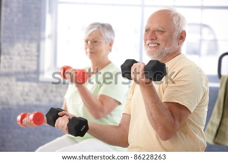 Senior people doing dumbbell exercises in the gym.? - stock photo