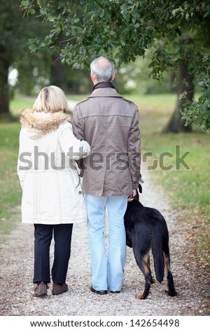 Senior people having a walk with dog - stock photo