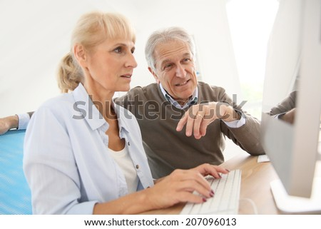 Senior people in office working on desktop computer
