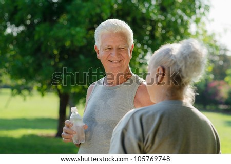 Senior people, old man and woman talking and drinking water after exercising in park
