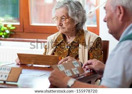Senior people playing rummy - stock photo