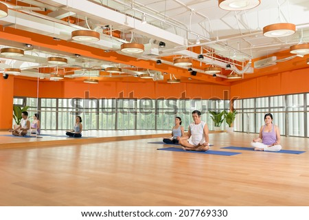 Senior people practicing lotus position at the fitness studio - stock photo