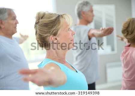 Senior people stretching out in fitness room - stock photo
