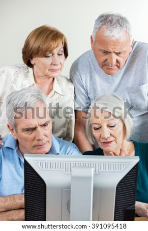 Senior People Using Computer Together In Classroom